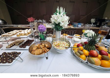 Buffet in hotel during breakfast, many fruits, bakery products and other food are on table