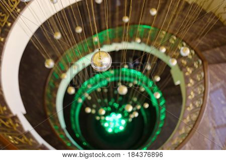 Empty spiral staircase with green illumination and hanging balls in hotel