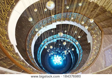 Beautiful spiral staircase with illumination and hanging balls in hotel