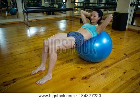 Determined woman exercising on fitness ball in gym