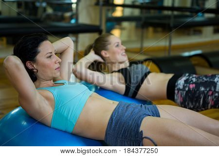 Fit women exercising on fitness ball in gym