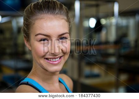 Portrait of smiling fit woman in fitness studio