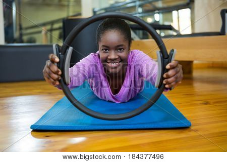 Portrait of smiling fit woman exercising with pilates ring in fitness studio