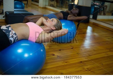 Two fit women performing pilate on exercise ball in fitness studio