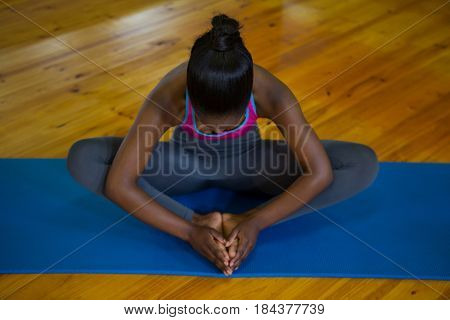 Fit woman doing stretching exercise on mat in fitness studio