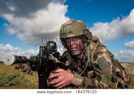 Normandy France- August 4 2011. Legionnaire in camouflage uniform with a rifle during training fire in the open area.