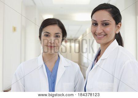 Smiling doctors in hospital hallway