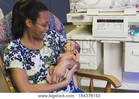 Nurse holding baby in rocking chair