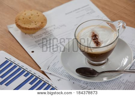 Coffee cup with spoon and documents on wooden background