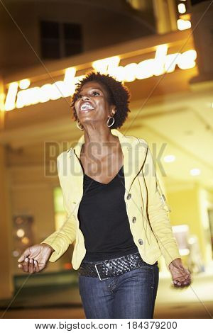 African American woman walking outdoors at night
