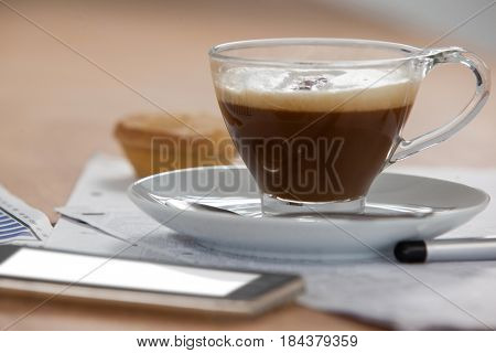 Cup of coffee and saucer on wooden background