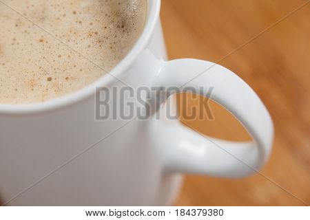 Close-up of white mug of coffee with creamy froth on wooden background