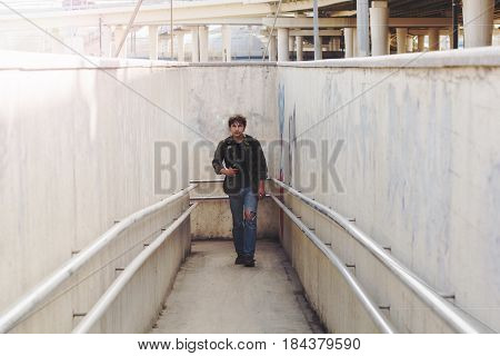 young man with a backpack coming out of the underpass