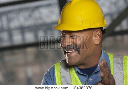 Hispanic worker in reflector-vest and hard-hat