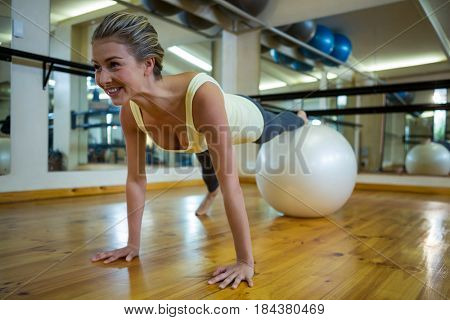 Smiling fit woman exercising on fitness ball in fitness studio