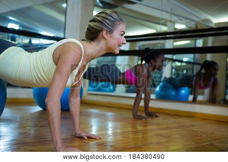 Smiling woman doing pilates exercises on fitness ball with coach in fitness studio
