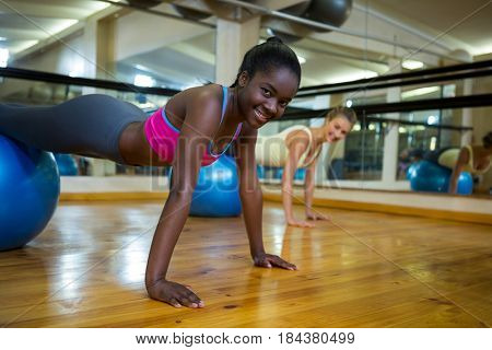 Portrait of smiling woman doing pilates exercises on fitness ball with coach in fitness studio