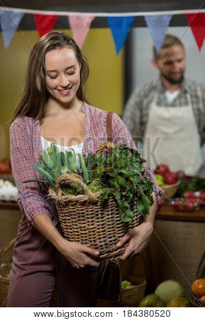 Smiling woman holding basket of green leafy vegetables in the grocery store