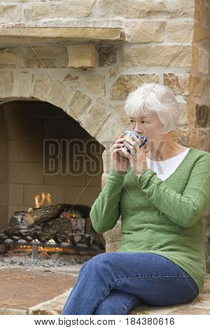 Mixed race woman drinking coffee near fireplace