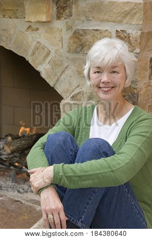 Mixed race woman sitting near fireplace