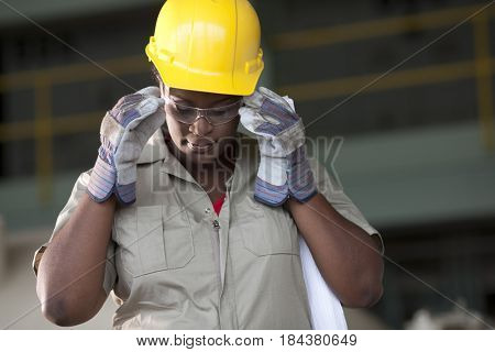 Black worker in hard-hat adjusting protective eyewear