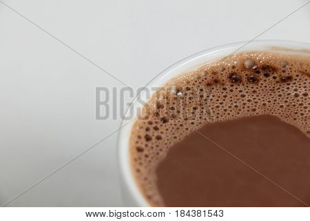 Close-up of white coffee cup with froth on white background