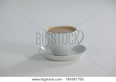 White cup of coffee with creamy froth on white background