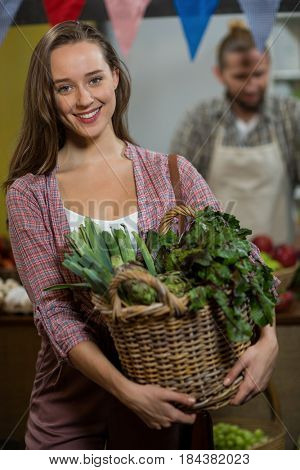 Portrait of smiling woman holding basket of green leafy vegetables in the grocery store