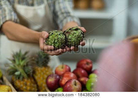 Close-up of a vendor offering custard apples at the counter in grocery store