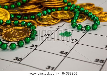 St. Patricks Day close-up of chocolate gold coins and beads kept on calendar