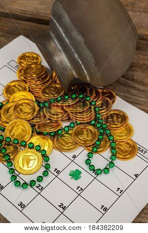 St. Patricks Day chocolate gold coins and beads kept on calendar on wooden table