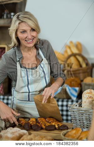 Saleswoman packing parcel for customer at counter in bake shop