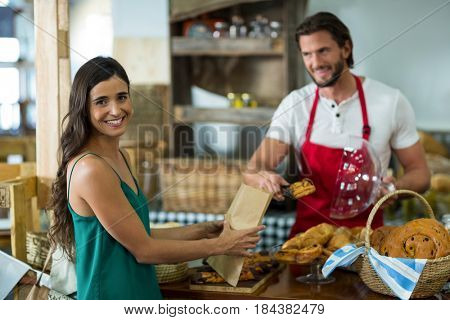 Smiling female customer receiving a parcel from bakery staff at counter in bake shop