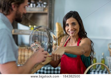 Portrait of smiling bakery staff giving parcel to male customer at counter in bake shop