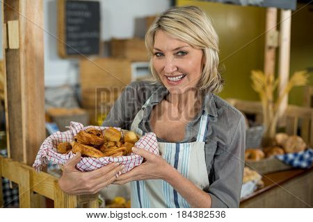 Portrait of smiling female staff holding a basket of baked snacks at counter in bake shop