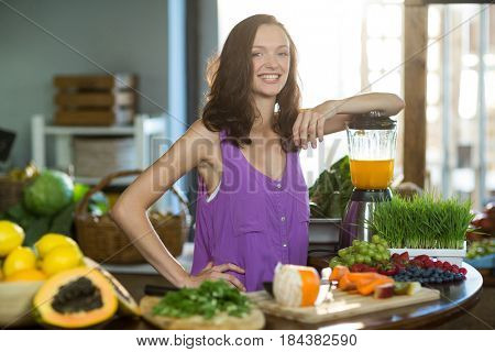 Smiling shop assistant standing at counter in health grocery shop