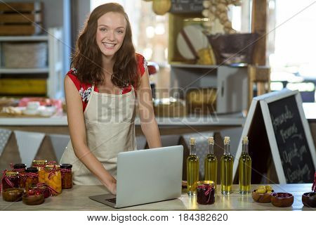 Portrait of a female shop assistant using laptop at the counter in grocery shop