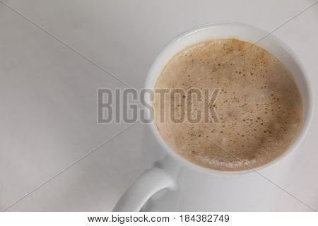 Close-up of white mug of coffee with creamy froth on white background