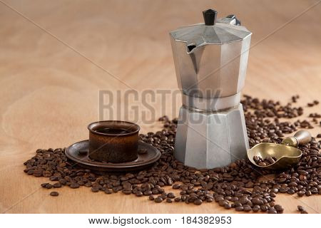 Coffee beans, coffee, coffeemaker and scoop on wooden background