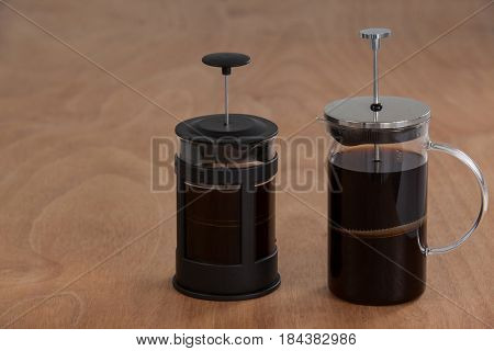 Cafetiere coffeemakers with black coffee on wooden background