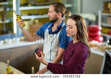 Shop assistants looking at olive oil and pickle bottles at grocery shop