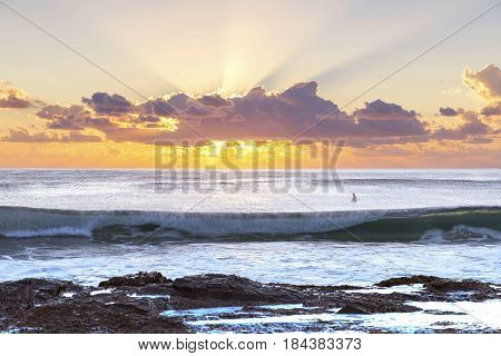 Sunrise eclipsing a large cloud as waves roll in from the ocean