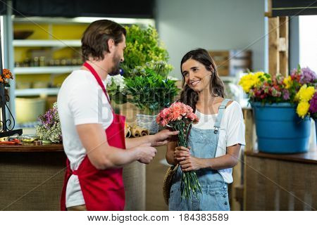 Florist interacting with female customer at florist shop