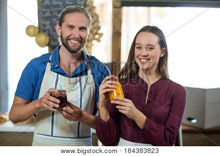 Portrait of shop assistants interacting while holding jam and pickle jar at grocery shop