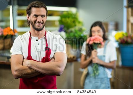 Portrait of a smiling florist standing in florist shop with arms crossed