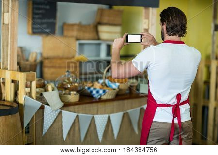 Rear view of bakery staff photographing bakery snacks and bread on the counter in bake shop