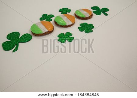 St. Patricks Day cookies decorated with irish flag surrounded with shamrocks on white background