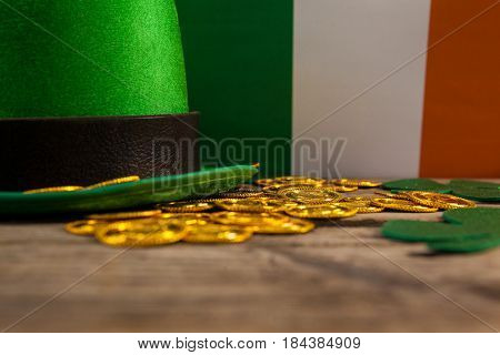 St Patricks Day leprechaun hat with shamrock and gold chocolate coin on wooden background