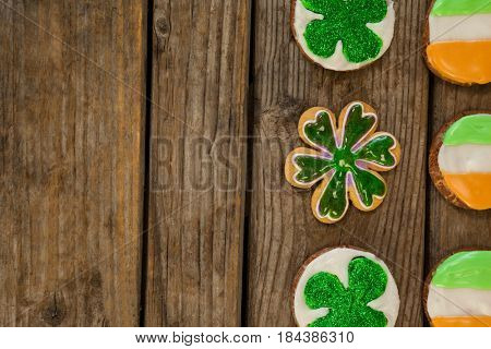 St. Patricks Day cookies decorated with irish flag and shamrock toppings on wooden background