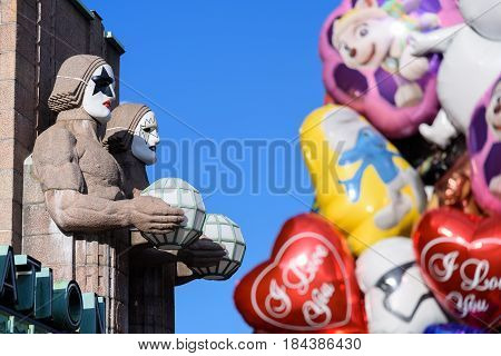 HELSINKI, FINLAND - MAY 1: Iconic stone men statues by the side of the entrance to the Helsinki Central Railway Station decorated as wearing heavy rock band Kiss masks during First of May celebrations with colourful balloons on the foreground May 1, 2017